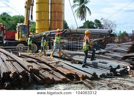 Group of construction workers lifting bundle of reinforcement bar using crane