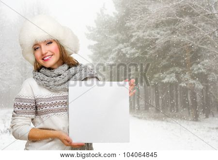 Young girl with empty poster at winter forest