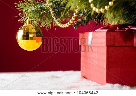 gift box on snow under christmas tree