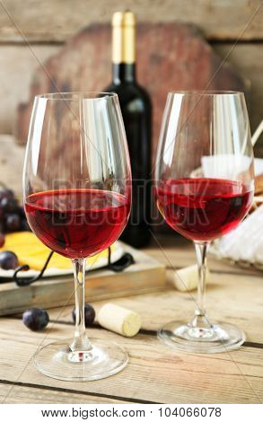 Still life of wine, grape, cheese and bread on rustic wooden background