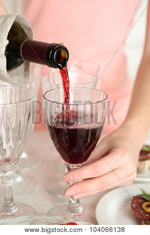 Woman pouring wine into glass, close up