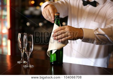 Portrait of handsome bartender with champagne bottle
