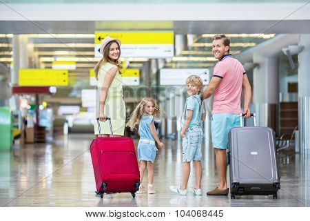 Family with suitcases in the airport