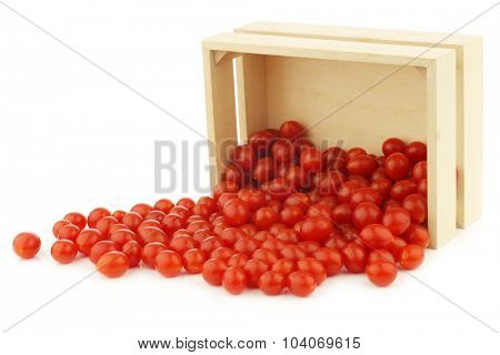fresh Tomberry (very small) tomatoes in a wooden crate on a white background