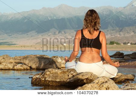 beauty girl in yoga pose on beach