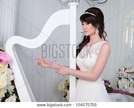 Portrait Of Beautiful Bride With Harp. Wedding Dress. Wedding Accessories