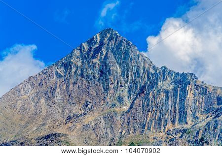 Scenery of high mountain peak over blue sky with white clouds.