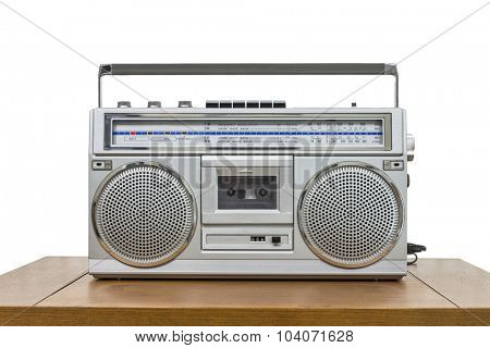 Vintage boombox on wood table isolated on white.