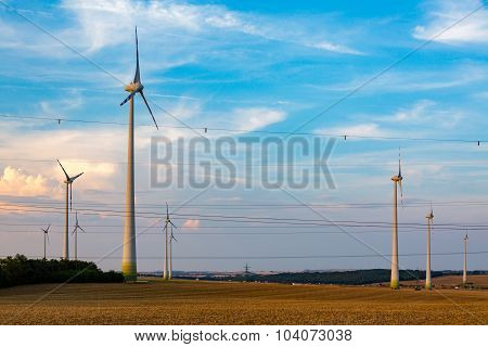 Powerlines And Windmills On The Field