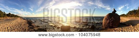 Woman sitting on a giant stone on a beach