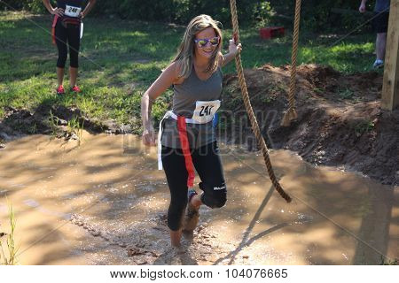 MUSKOGEE, OK - Sept. 12: Runners go through a muddy pond in hopes to avoid bloody zombies during the Castle Zombie Run at the Castle of Muskogee in Muskogee, OK on September 12, 2015.