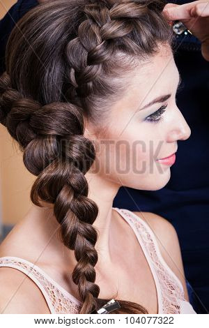 a woman with plait in the barbershop