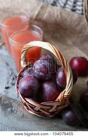 Delicious plum juice with fruits on table close up