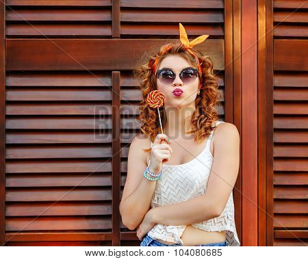 Pin-up Girl In Sunglasses Holding Lollipop.