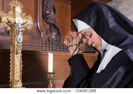 Closeup of a young nun in prayer