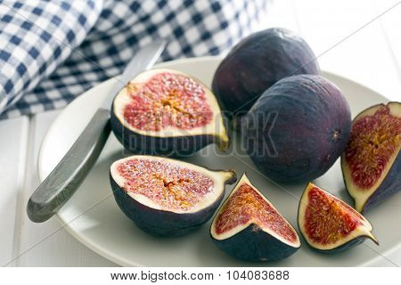 sliced fresh figs on plate with knife