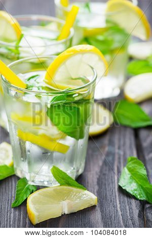 Lemonade with fresh lemons and mint in glasses on rustic wooden background