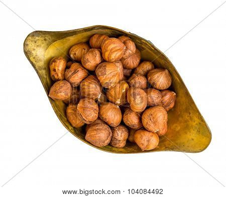 hazelnuts in a metal cup isolated over white