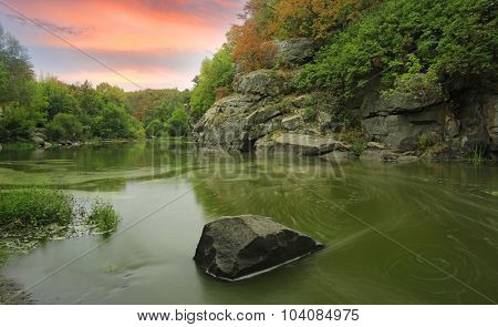 Evening scene on rocky river shore