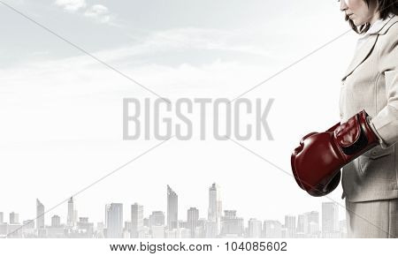 Young businesswoman in red boxing gloves competition ready