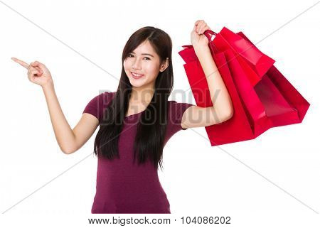 Asian young woman hold with shopping bag and finger point aisde