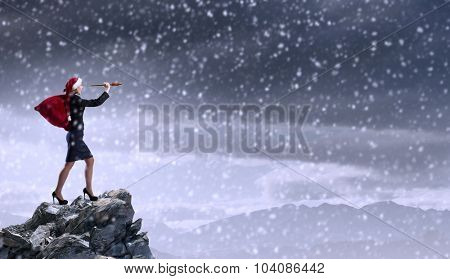 Woman in formal suit and Santa hat looking in spyglass
