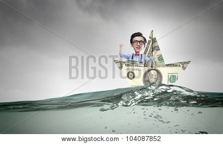 Businessman escapes from crisis on paper boat made of dollar banknote