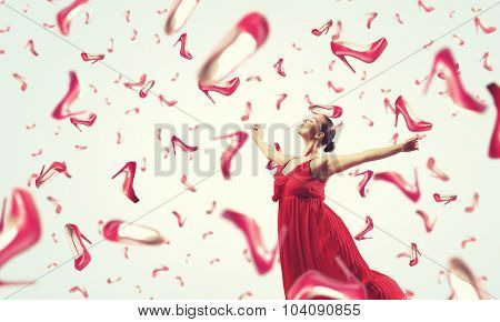 Young cheerful woman in dress and many falling shoes