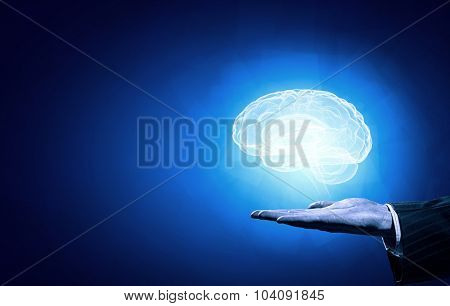 Close up of human hand holding brain on blue background