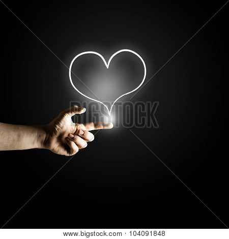 Man's hand pressing heart icon button on digital touch screen