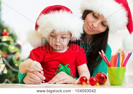 child girl and mother writing letter to Santa