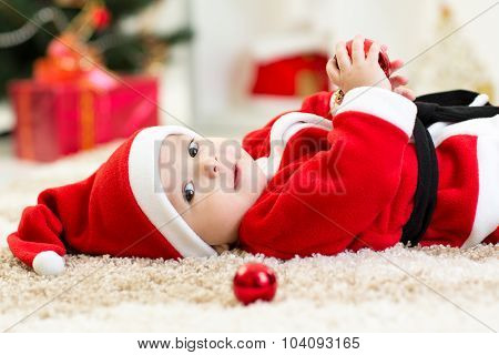 Baby boy weared Santa lying near Christmas tree