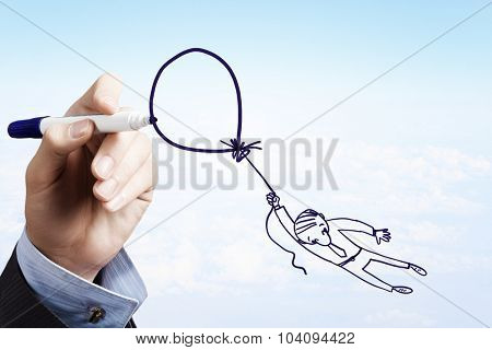 Man hand drawing caricature of businessman flying on balloon