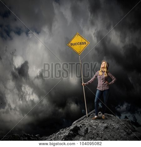 Young woman satnding on rock top with signboard