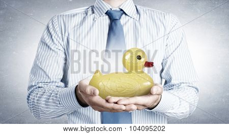 Businessman holding in hands yellow toy rubber or plastic duck