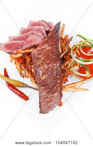 meat food : rare beef on potato chips with pepper and tomatoes over plate isolated on white background