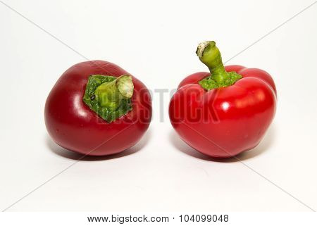 Two Ripe Red Peppers On Over White