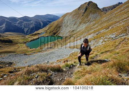 Backpacker Lady Hiking By The Lake In The Mountains