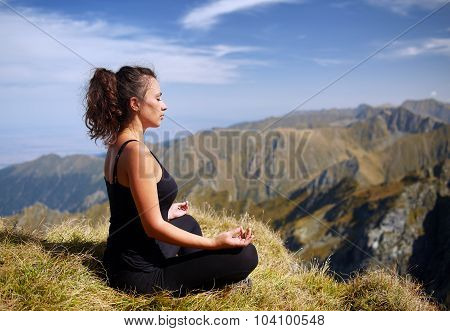 Woman Practicing Yoga On Mountain