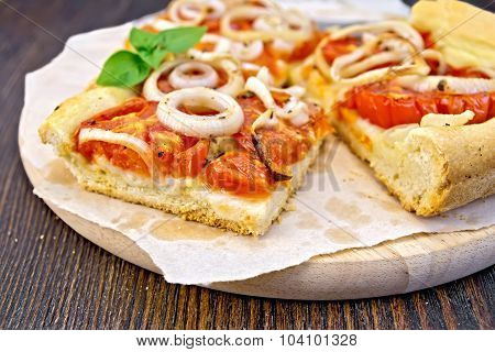 Pie with onions and tomatoes on paper