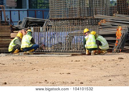 Construction workers fabricating pile cap reinforcement bar at construction site