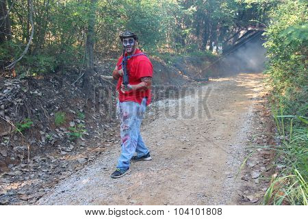 MUSKOGEE, OK - Sept. 12: A zombie man roams down the road in wait for athlete during the Castle Zombie Run at the Castle of Muskogee in Muskogee, OK on September 12, 2015.