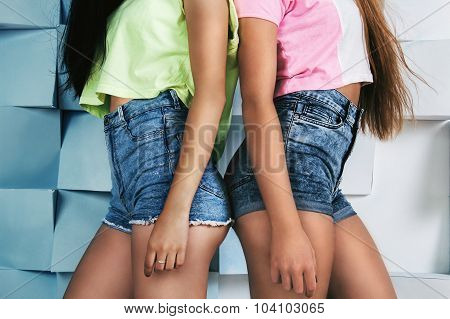 Two Young Fit Girls In High Waistline Jeans Shorts And Bright Colored T-shirts