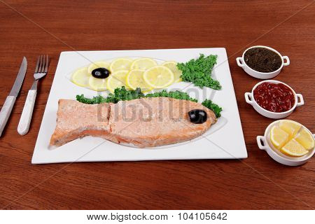 healthy food fresh roast red fish salmon with kale lemon antipesto ketchup sauce on white plate over wooden table
