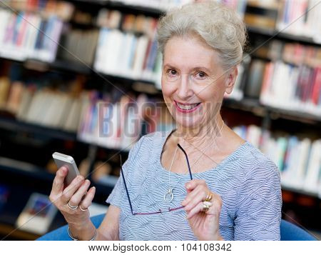 Elderly lady with mobile phone in library