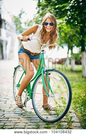 Happy bicyclist in eyeglasses looking at camera in park