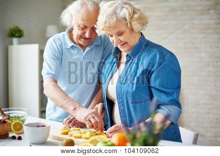 Happy senior man and woman cutting fruits in the kitchen