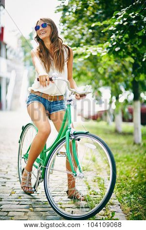 Pretty woman in eyeglasses riding bicycle