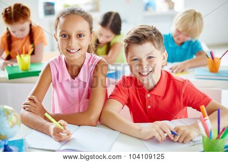 Friendly schoolchildren looking at camera while sitting by desk