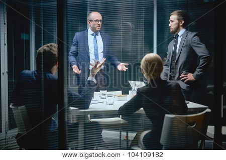 Modern business people sharing ideas and voicing opinions in office